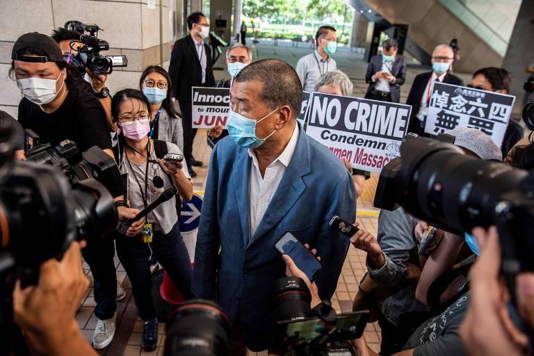 O ativista pró-democracia Jimmy Lai (centro) conversa com jornalistas após deixar tribunal de Hong Kong nesta quinta (15)