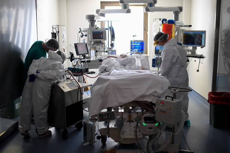 Equipe médica, com roupas de proteção, atendem paciente em maca