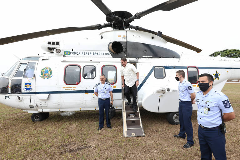 homem de camisa branca desce de escada de helicóptero, observado por três militares