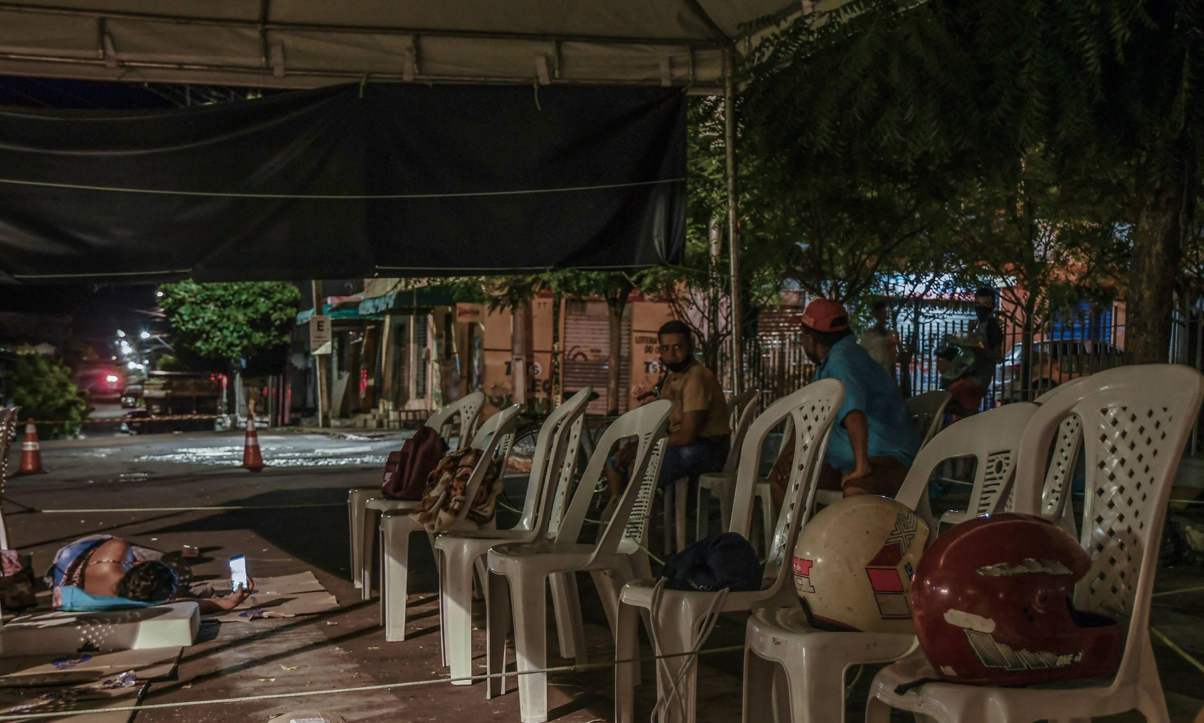 Moradora de Crateús é vista no chão em fila por auxílio emergencial; sobre cadeiras, capacetes marcam lugares que serão vendidos por até R$ 50