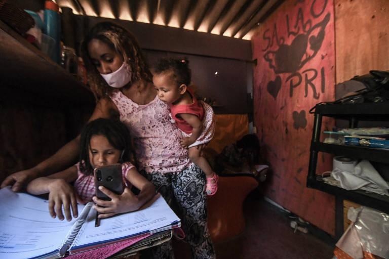 Uma menina sentada numa mesinha com livros segura um celular e sua mãe ajuda ela, segurando um bebê no colo, dentro de um pequeno salão de beleza.
