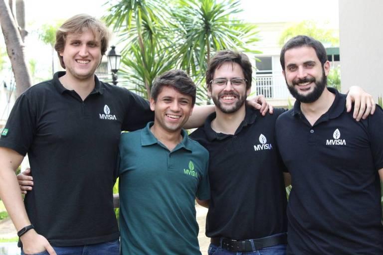 Três homens com camiseta preta e um com camiseta verde