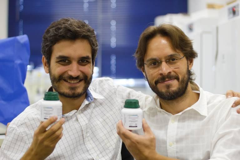 Dois homens com camisa branca sorrindo e segurando frascos