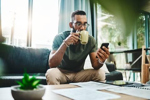 Foto de um jovem usando um smartphone enquanto analisa suas finanças em casa