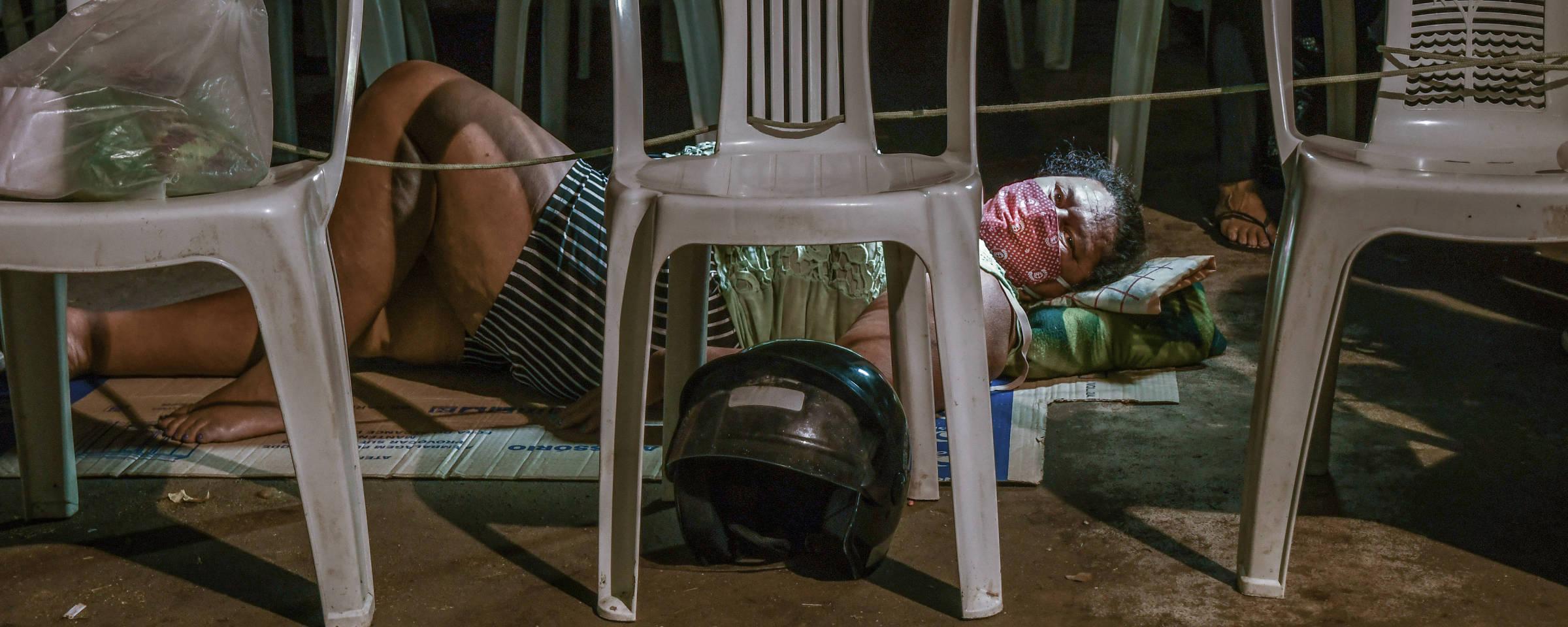 cadeiras de plástico enfileiradas com capacetes e bolsas em seus acentos. Mulher deitada no chão entre as cadeiras