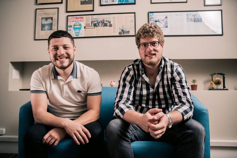 Dois homens sentados em sofá azul, sorrindo