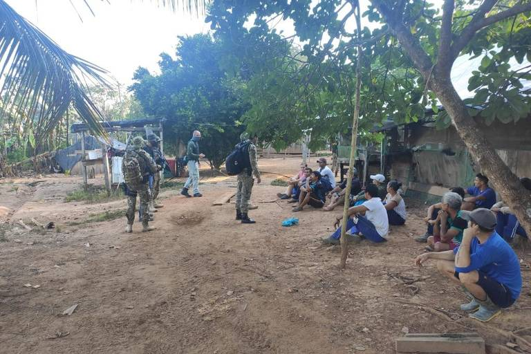 Agentes em pé e civis sentados na terra, olhando para os oficiais