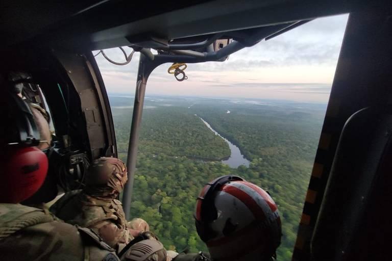 Agentes olham para a floresta de dentro do helicóptero; é possível ver a curva de um rio