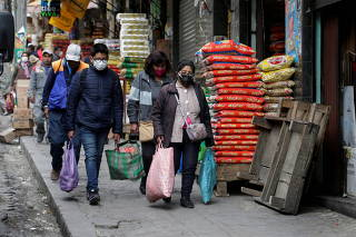 People carry groceries at the Rodriguez market in La Paz