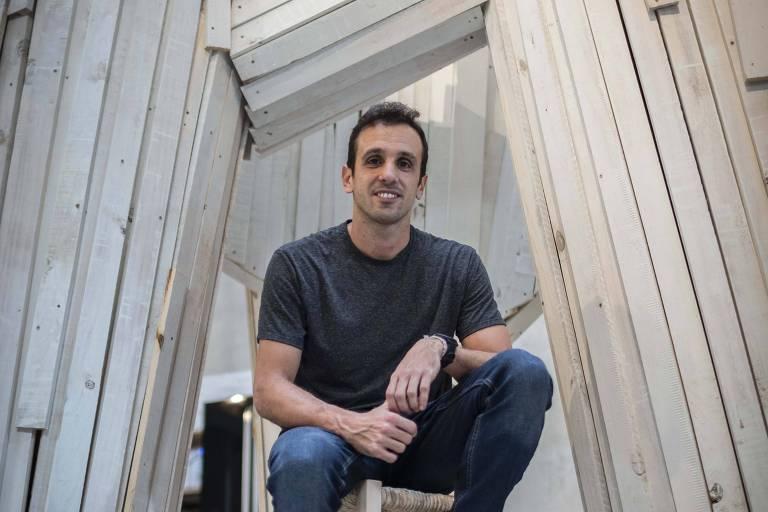 Homem sentado, sorrindo, com estrutura de madeira atrás dele