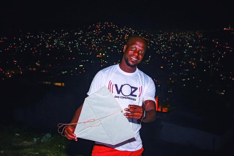 homem negro com pipa na mão em frente a favela