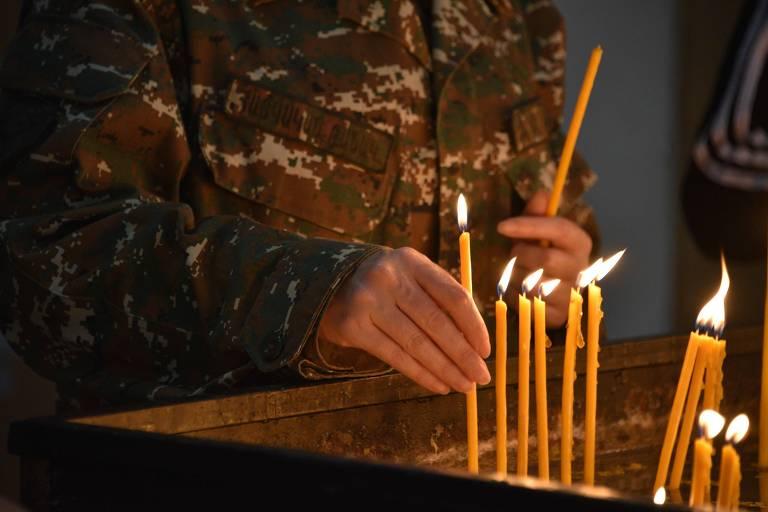 Cidadão armênio acende vela em igreja de Ierevan em lembrança aos mortos no conflito com o Azerbaijão