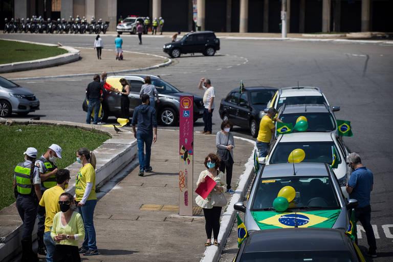 Carros adornados com cores da bandeira brasileira estão estacionados em fila; ao fundo, policiais da Cavalaria observam movimentação