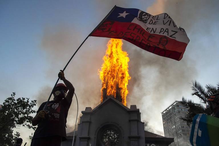Manifestante agita bandeira em frente a igreja incendiada em Santiago, no Chile