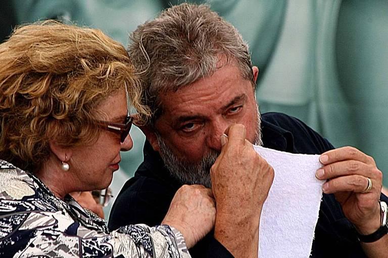 Lula, de camisa escura, segura papel em frente à boca para falar com Marisa Letícia, de camisa estampada preta e branca. Atrás, painel preto e branco com foto de mulher com criança