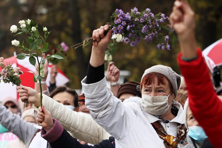 Manifestantes, usando máscaras de proteção, seguram flores com os braços erguidos durante o protesto