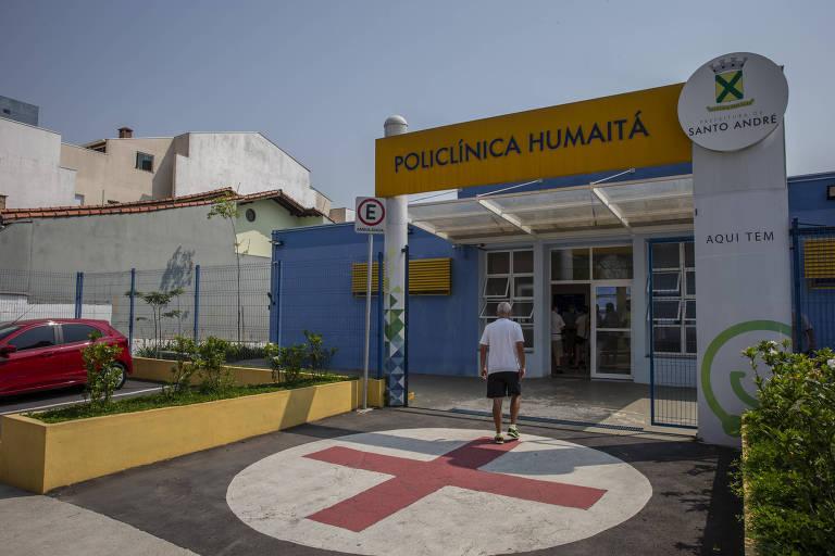 Entrada de uma unidade de saúde pintada de azul e amarelo, com canteiros na parte da frente e uma grande cruz vemelha num círculo branco na entrada