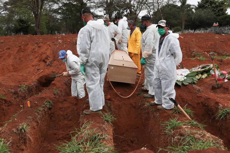 Coveiros com uniformes brnacos contra o novo coronavírus seguram caixão de madeira antes de enterrá-lo no cemitério da Vila Formosa, em São Paulo