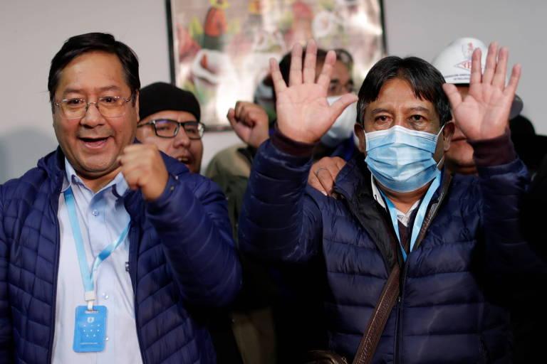 O presidente eleito na Bolívia, Luis Arce, à esq., ao lado do vice eleito, David Choquehuanca, de máscara, em La Paz