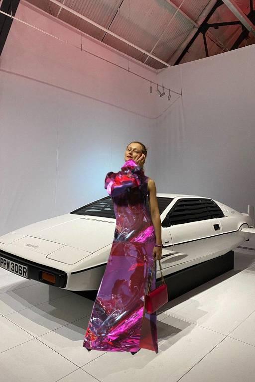 Mulher em frente de carro branco usa vestido metálico rosa