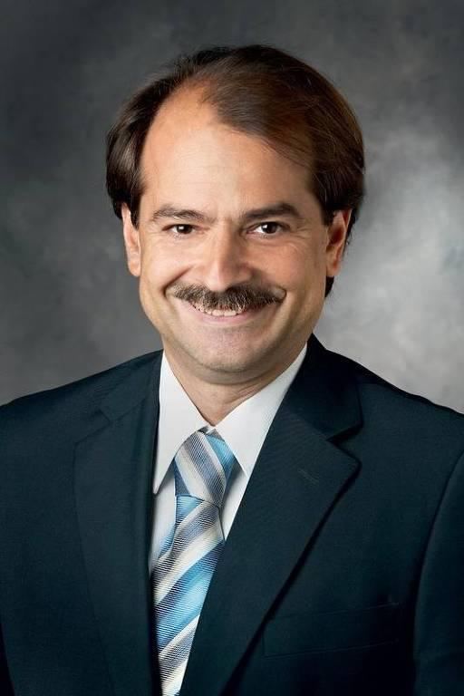 Homem branco de meia idade e bigode usando terno e gravatas azuis sorri olhando a ...</div></div>                                         <div class=