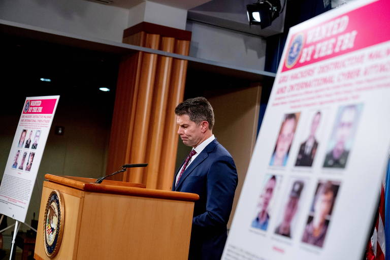 David Bowdich, do FBI, fala ao lado de cartaz com fotos de russos apontados como responsáveis pelos ataques