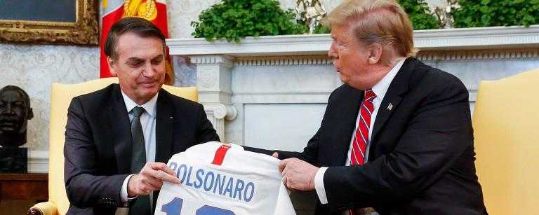 Donald Trump, presidente dos Estados Unidos, entrega uma camisa personalizada ao presidente Jair Bolsonaro
