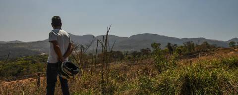 BRUMADINHO/ MINAS GERAIS / BRASIL - 07/09/20 - :00h - RAIO X SOBRE A COVID NAS REGIÃO SUDESTE E NORDESTE DO BRASIL. Marcos Aurélio de Oliveira, 52  carreteiro, observa local onde a barragem foi rompida.   ( Foto: Karime Xavier / Folhapress) . ***EXCLUSIVO***Especial - O Brasil das várias pandemias  #PraCegoVer Homem , de costas, em meio a um campo verde com montanhas ao fundo,  segura capacete de moto enquanto observa local onde a barragem se rompeu