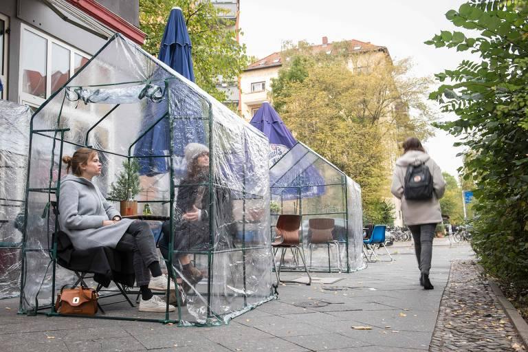 Clientes estão sentados dentro de pequenas barracas transparentes