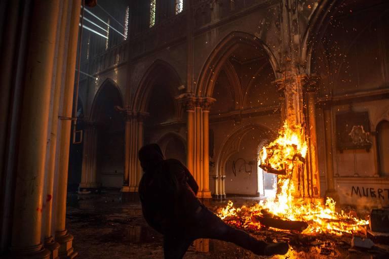 Manifestante incendeia a igreja de São Francisco de Borja durante protesto em Santiago, no Chile