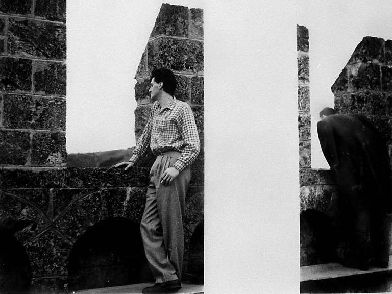 homem jovem de terno apoiado em mureta de tijolo