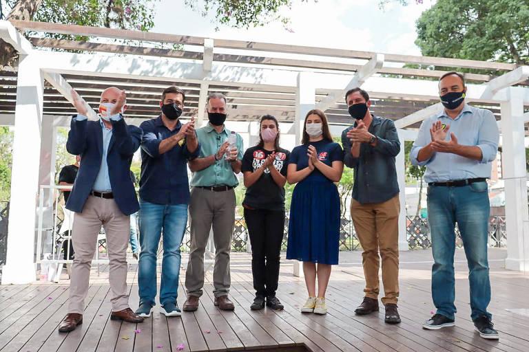 Sete candidatos à prefeitura de Curitiba, cinco homens e duas mulheres, aparecem lado a lado posando para foto em praça pública