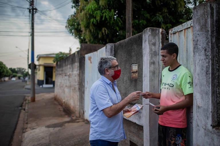 homem de camisa azul e máscara vermelha entrega panfleto a morador