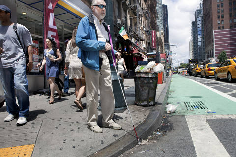 Ken Stewart, who is blind, navigates streets with the aid of a cane and mental maps, in New York, June 26, 2012. Over the past few years, sweeping changes to the city have made it harder and harder for the blind to rely on their mental maps. (Sara Krulwich/The New York Times)