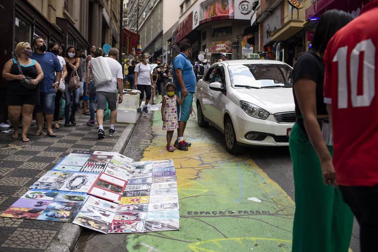 Mercadorias de ambulantes em cima da faixa para pedestres