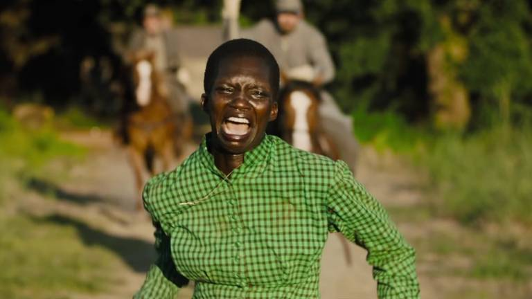 Pessoa negra corre aos gritos e choros enquanto dois homens cavalgam atrás