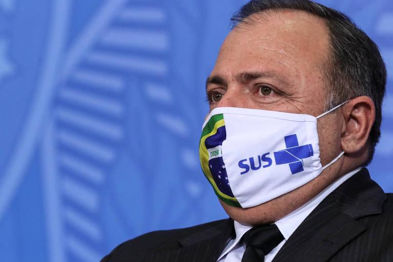 Ministro com máscara dividida ao meio; de um lado, o símbolo do SUS, do outro, a bandeira brasileira