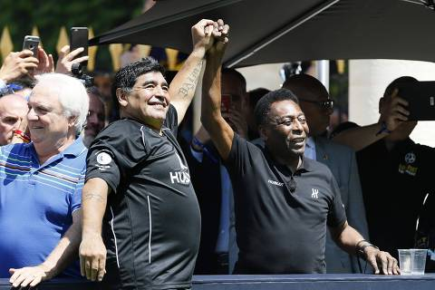 TOPSHOT - Former Argentinian football international Diego Maradona (L) and former Brazilian footballer Pele attend a football match organised by Swiss luxury watchmaker Hublot at the Jardin du Palais Royal in Paris on June 9, 2016, on the eve of the Euro 2016 European football championships. / AFP PHOTO / PATRICK KOVARIK ORG XMIT: 10724