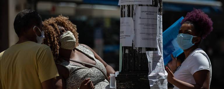 Mulheres olham poste com anúncios de vagas de emprego