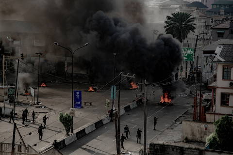 Armed men are seen near burning tires on the street, in Lagos, Nigeria October 21, 2020, in this image obtained from social media. UnEarthical/via REUTERS THIS IMAGE HAS BEEN SUPPLIED BY A THIRD PARTY. MANDATORY CREDIT. NO RESALES. NO ARCHIVES. ORG XMIT: LAG01
