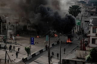 Armed men are seen near burning tires on the street, in Lagos