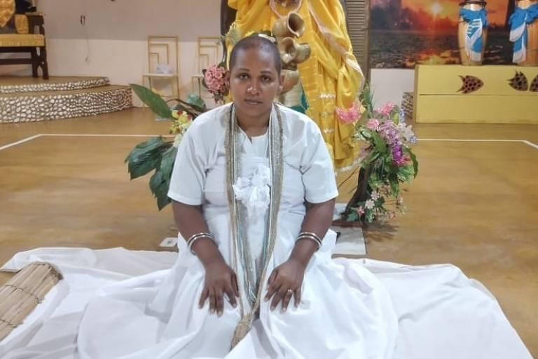 Mulher com roupas brancas de candomblé e cabelos raspados em meio a uma sala com objetos do candomblé