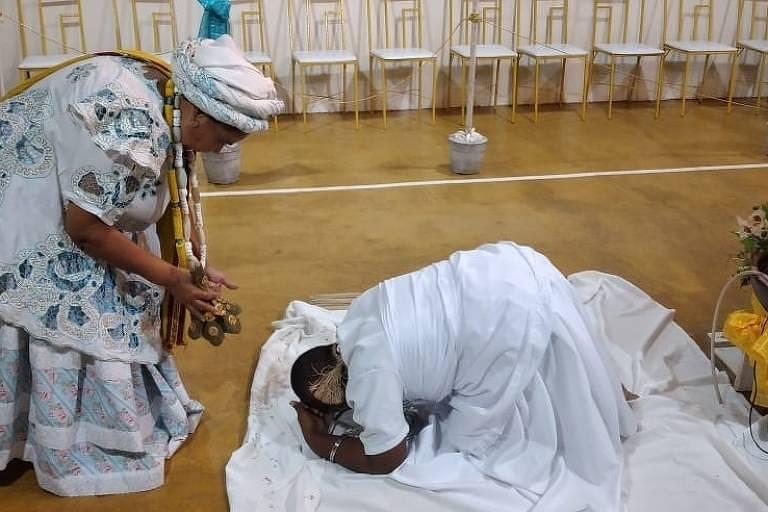 Uma mãe de santo está em frente a uma mulher ajoelhada aos seus pés, com roupas de candomblé