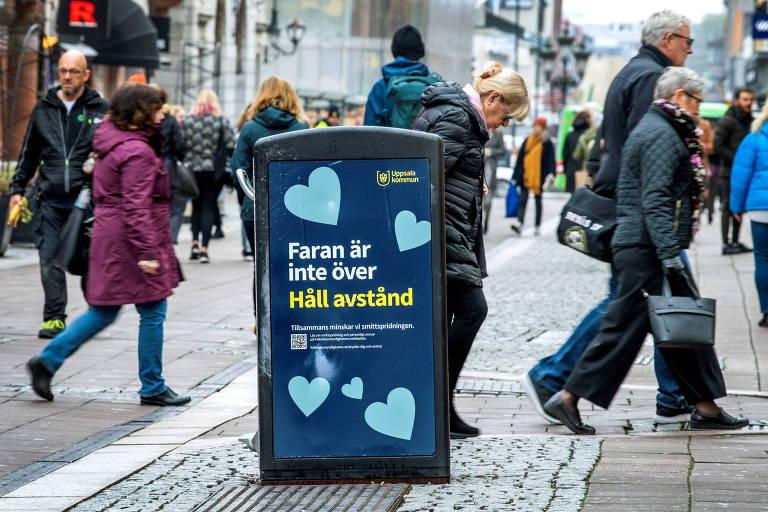 Pessoas caminham em rua movimentada; em destaque no centro da foto há uma lata de lixo com um aviso para as pessoas manterem distância
