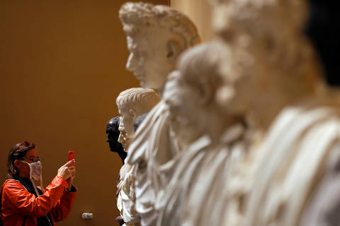 A woman takes a picture of a statue from the