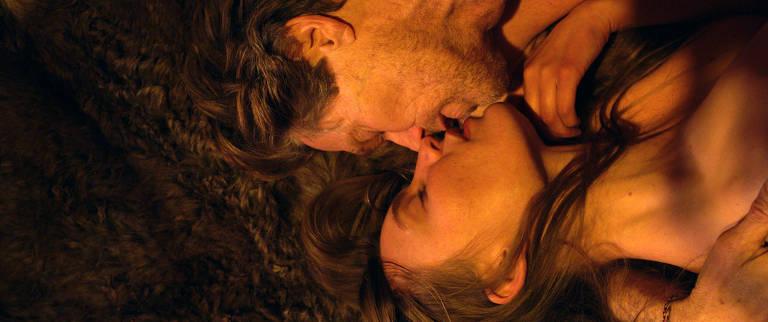 Homem com barba por fazer está deitado em cima de mulher e a beija