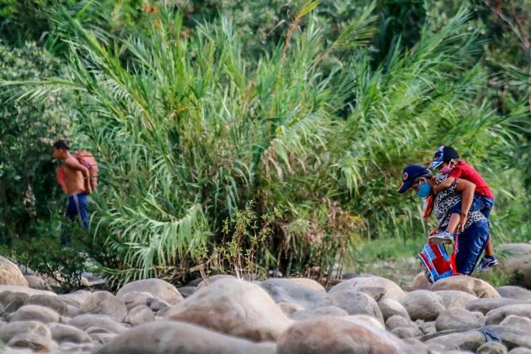Migrantes venezuelanos fazem caminho por área de mata para tentar entrar no território colombiano, nas proximidades da cidade de Cúcuta