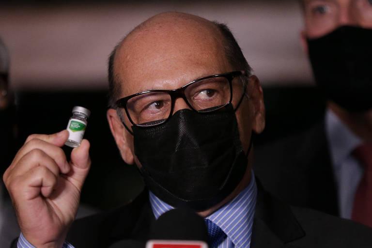 Homem calvo de máscara e óculos segura ampola