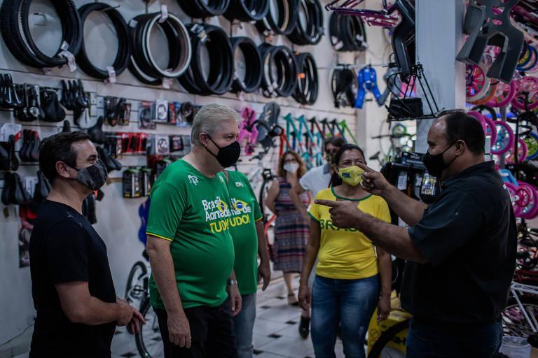 homem de máscara e camisa verde conversa com outro