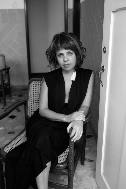 Karla Monteiro sentada em uma cadeira